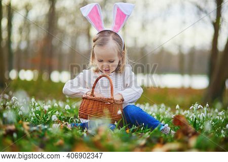Girl Wearing Bunny Ears Playing Egg Hunt On Easter. Toddler Sitting On The Grass With Many Snowdrop