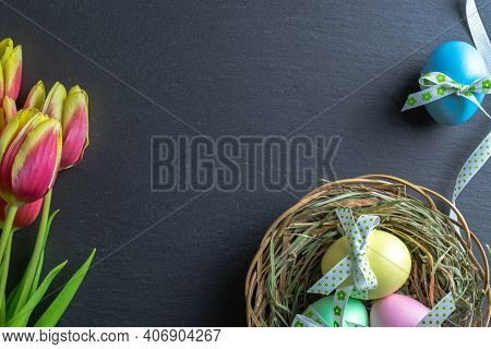 Easter Background Blue. Colorful Egg With Tape Ribbon, Spring Tulips On Dark Rough Stone Background
