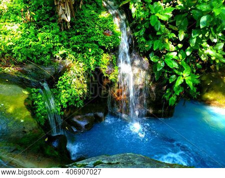 Blue Water That Flows And Falls On The Sidelines Of The Leaves