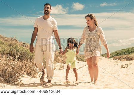 Happy Parents And Cheerful Kid Wearing Summer Clothes, Walking Along Sand Path, Girl Holding Parents