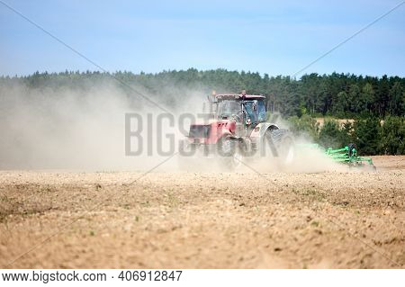 Tractor Is Plowing Field With Harrow. Typical Agricultural Scene Tractor Cultivation In Field In Clo