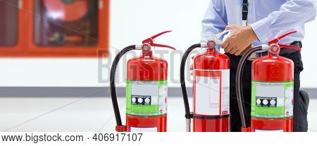 Firefighter Checking The Handle Of The Red Fire Extinguishers Tank In The Building Concepts Of Preve
