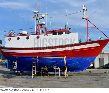 Old Traditional Blue, Red And White Galician Fishing Boat In A Harbour. Galicia, Spain.