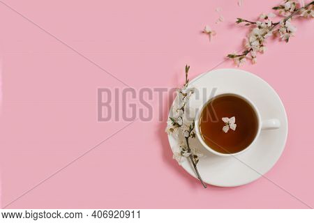 White Porcelain Cup With Black Tea. Branches Of A Blossoming Apple Tree Lie On A Gentle Pink Backgro