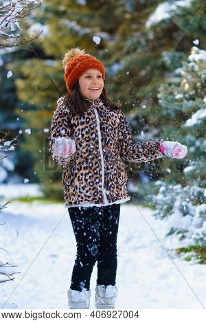 child girl throws up snow and playing in the winter forest, bright snowy fir trees, beautiful nature.