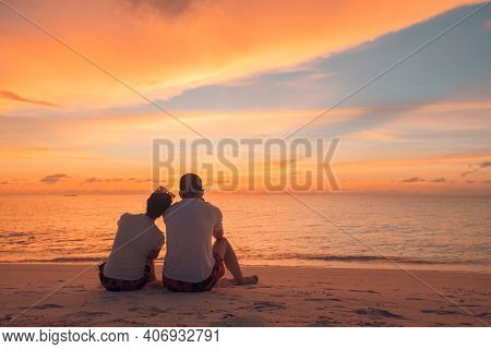 Romantic Couple On The Beach At Colorful Sunset On Background. Honeymoon Couple Sitting On Sunset Be