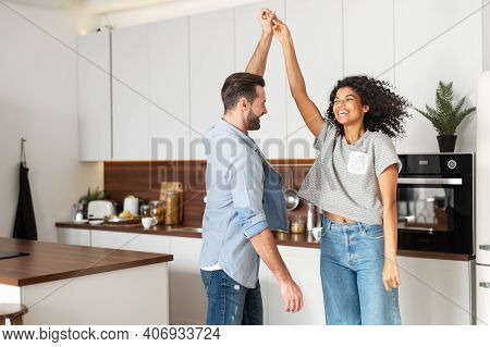 Happy Young Multi Ethnic Couple In Love Dancing And Holding Hands In The Kitchen. Joyful Boyfriend A