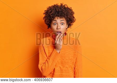 Indoor Shot Of Shocked Young Curly African American Woman Dressed In Casual Jumper Keeps Mouth Opene