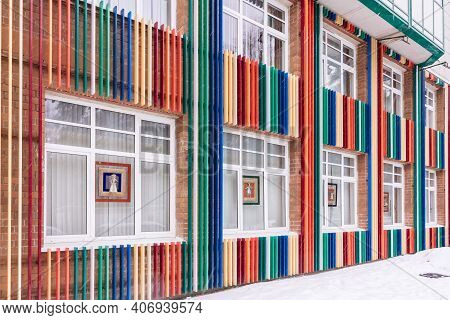 Bright Commercial Public Building Or Pavilion With Facade Of Multi-colored Strips. Detail Facade Wit