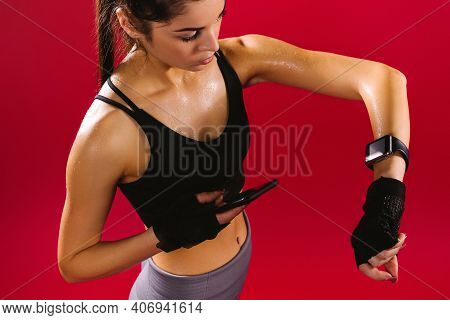 Tired Fitness Woman Sweating Taking A Break On Phone After Difficult Training, Tracking Time Using H