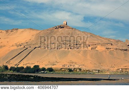 A View From The River Nile Of The Cliff Face Which Hosts Various Ancient Egyptian Tombs (their Entra