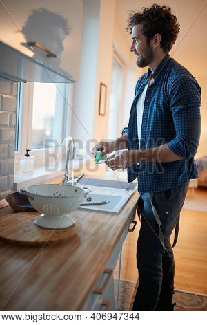 Young man enjoying doing housework in a relaxed atmosphere in the kitchen. Kitchen, housework, quarantin, home