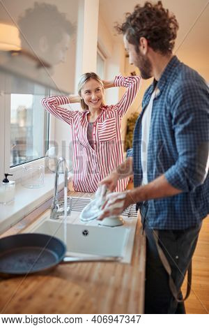 A young couple doing housework in a relaxed atmosphere in the kitchen together. Kitchen, housework, home, relationship