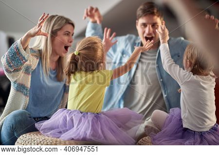 Young parents imitating monsters with their little daughters in a cheerful atmosphere at home. Family, home, playing