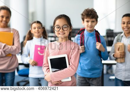 Pupils, Technology And Learning Concept. Smiling Asian Girl In Eyeglasses Holding Digital Tablet And