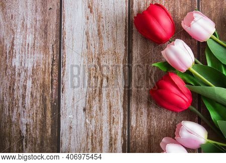 Bouquet Of Pink And Red Tulips On A Brown Wooden Background. Background For Design. Spring Backgroun