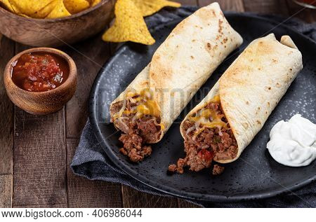 Burritos With Ground Beef, Refried Beans And Cheese On A Black Plate With Salsa And Tortilla Chips