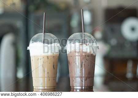 Close Up Of Iced Cocoa Cool Drink And Iced Coffee Mocha Are In Plastic Glass Arranging In Cafe Backg