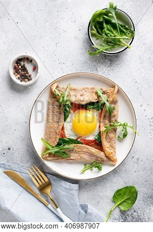 Buckwheat Crepe Galette With Egg, Ham And Spinach On Gray Background. Traditional French Dish. Verti