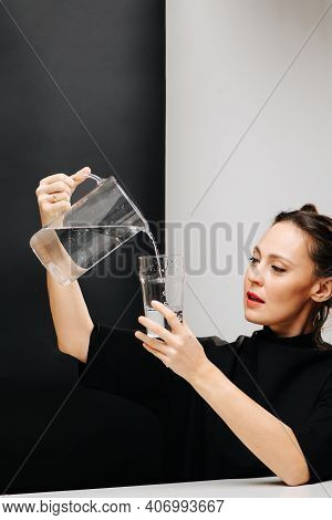 Eccentric Woman Pouring Water In A Glass From A Jug, Holding On A Head Height