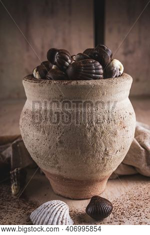 Shell Shaped Chocolates With Cream In A Clay Jar