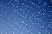 Close up of a soccer net and blue sky. poster