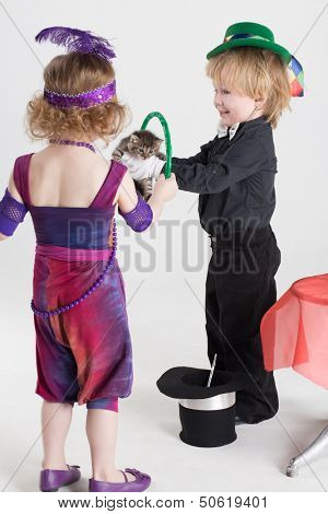 Little boy and girl in costume magicians shows trick with a kitten and rings, focus on the boy poster