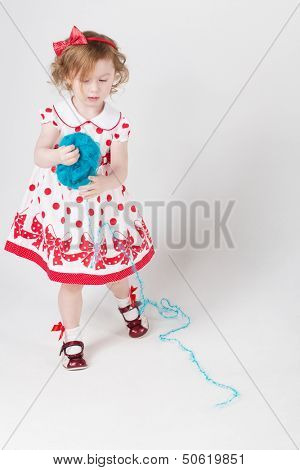 Little girl in a polka dot dress unravels the tangle of blue yarn