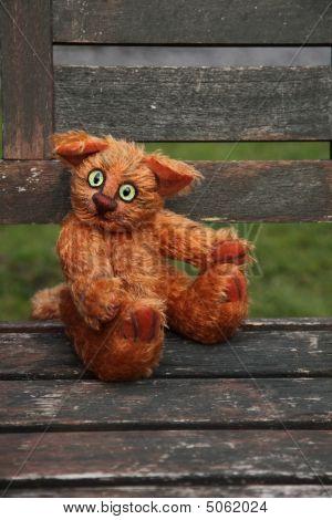 Stuffed Ginger Cat Sitting On Old Wooden Garden Chaiir