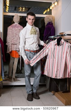 A man in a white shirt with jabot chooses clothes in a clothing store
