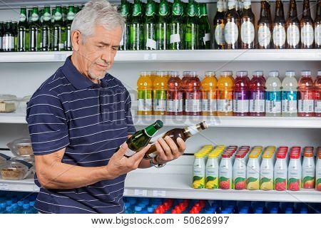 Senior man comparing beer bottles at supermarket