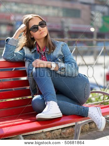 Girl In Jeans Sitting On A Bench In The Street
