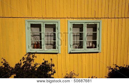 yellow wooden wall with two windows.jpg