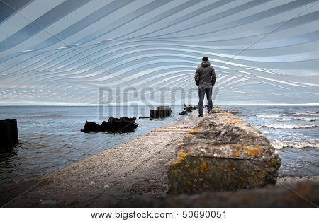 A Man On The Old Broken Pier Starring At The Abstract Sea Landscape With Wave Stripes Against The Cl