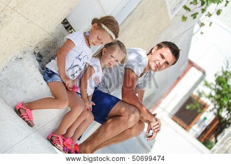 Young Father And His Daughter Sitting On Doorstep Of Old House On Street In Emporio, Santorini
