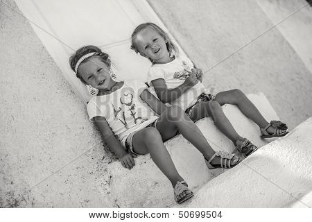 Little Cute Sisters Sitting Near Old House In Greek Village Of Emporio, Santorini