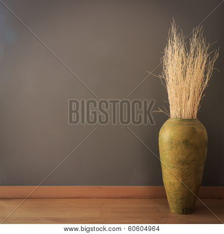 gray wall background with vase of dry branch