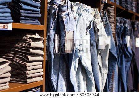 Fashion clothes on shelves in store.