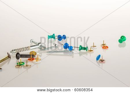 Tacks and screws on white background