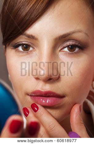 beautiful woman smartens up in front of compact mirror poster