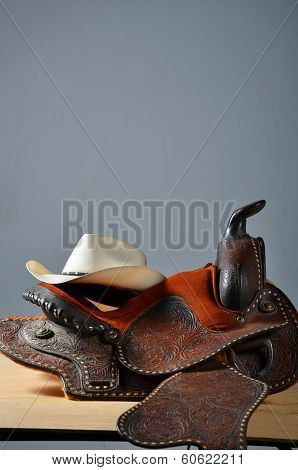 Western hat on a well used western saddle with a padded seat. poster