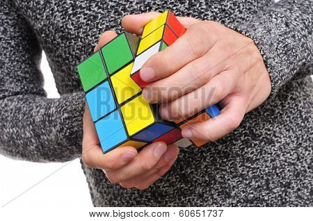 TARRAGONA, SPAIN - FEBRUARY 3, 2014: A man trying to solve a Rubiks cube. This famous cube puzzle was invented by the architect Erno Rubik in 1974
