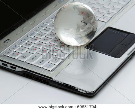 Crystal-glass globe on keyboard of modern notebook