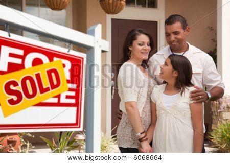 Familia hispana frente a su nuevo hogar con signo vendido