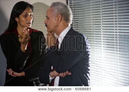 Multi-ethnic businesspeople having discreet conversation in corner of meeting room