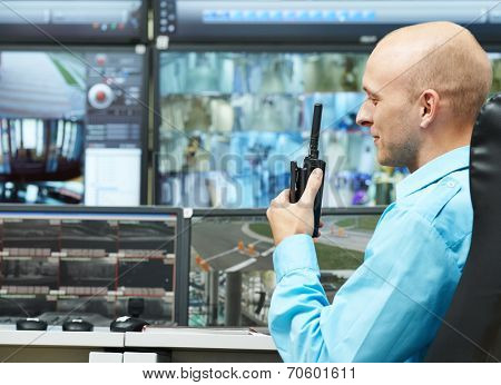 security guard watching video monitoring surveillance security system with portable radio transmitter