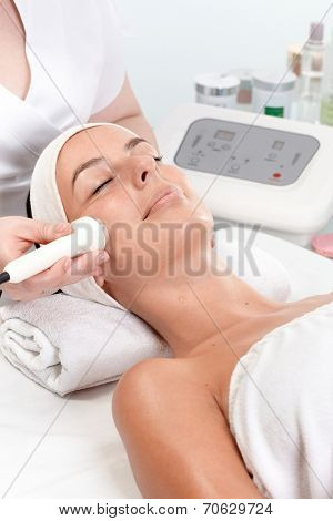 Young woman getting skin rejuvenating treatment in beauty saloon, laying eyes closed.