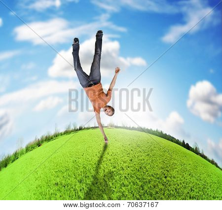 a woman doing a cartwheel on an upside down planet of green grass