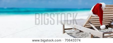 Panorama of sun chair with Santa hats on beautiful tropical beach with white sand and turquoise water, perfect Christmas vacation