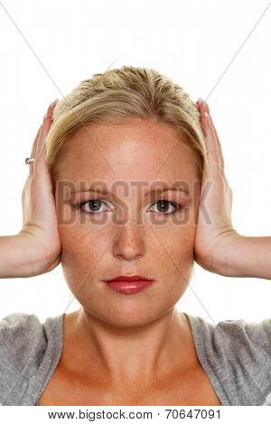 a young woman holding her ears. symbol photo for do not want to hear disputes and conflicts, as well as loud undtinnitus